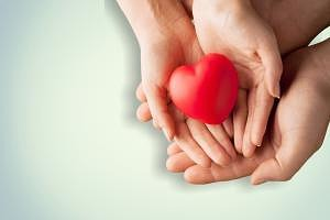 People holding a red heart in their hands